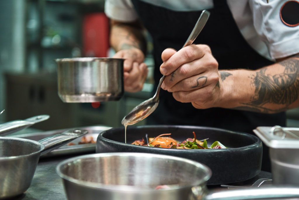 Image: A chef preparing a dish. Read an interview with Eric Rocha, 105 Noshery chef.